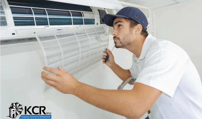 Air conditioning maintenance technician examines residential HVAC system.