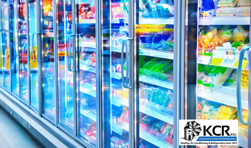 Row of commercial freezers containing food in supermarket aisle.