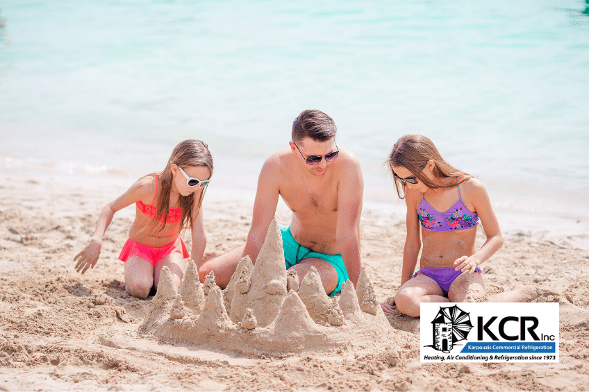 Father and two daughters build sand castle on beach during summer vacation; air conditioning maintenance.