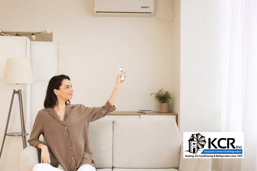 Woman at home on couch adjusting air conditioner for best temperature with remote control.